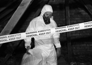 Operator in correct PPE to handle asbestos, behind warning tape