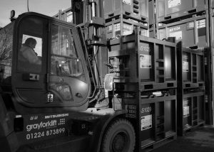 Operator moving Augean North Sea Services containers with forklift